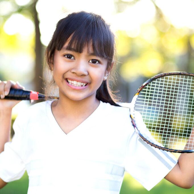 Closeup cute little asian girl holding a badminton racket, Outdoor